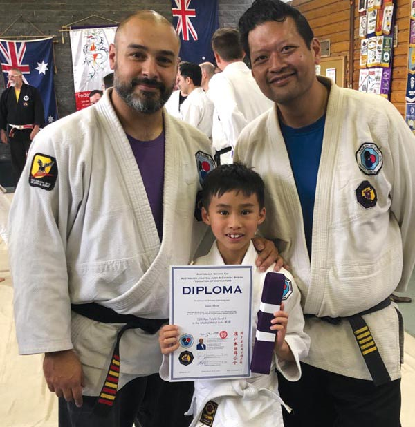 Young JiuJitsu student receiving his first belt