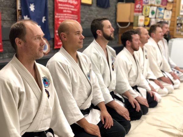 JiuJitsu students kneeling to observe teaching